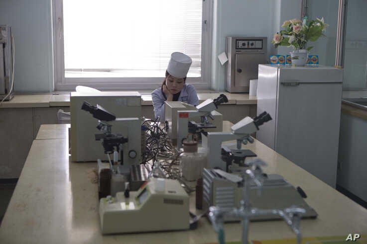 In this Feb. 20, 2013 photo, a nurse sits inside a laboratory as guests tour the Pyongyang Maternity Hospital in Pyongyang,…