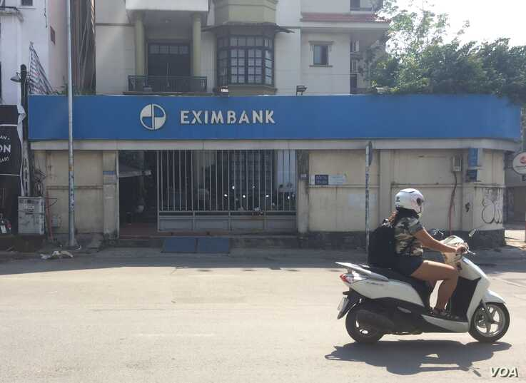A motorbike driver rides past a branch of Eximbank in Ho Chi Minh City. (H. Nguyen/VOA)