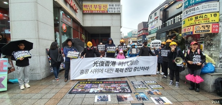 """South Korean college students and activists in Seoul's Hongdae district participate in a demonstration in support of Hong Kong's pro-democracy protests on November 24, 2019. The main banner reads """"Stop the Violent Suppression of Hong Kong Protesters."""" VOA/Lee Juhyun"""