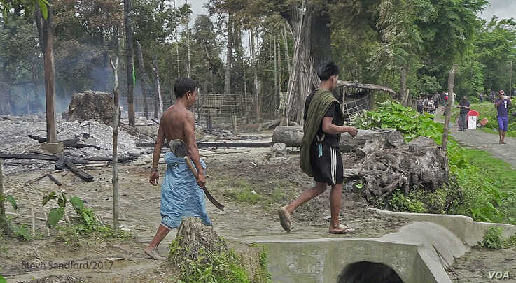 Men seen burning huts in the town of Maungdaw, Myanmar. (Photo: Steve Sandford / VOA)