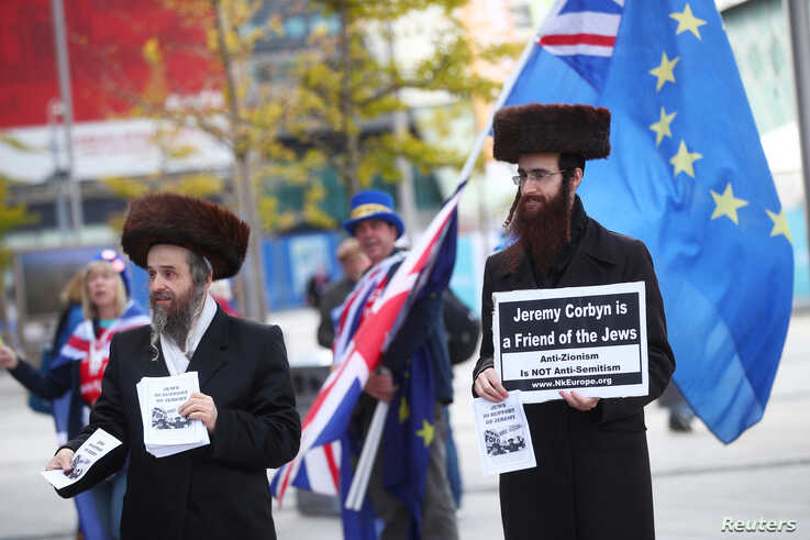 Two men wearing Orthodox Jewish attire hold placards and leaflets in support of Labour Party leader Jeremy Corbyn outside the…