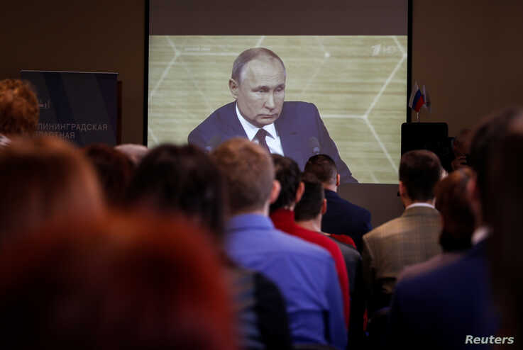 People watch a broadcast of Russian President Vladimir Putin's annual end-of-year news conference, in a library in Kaliningrad,…