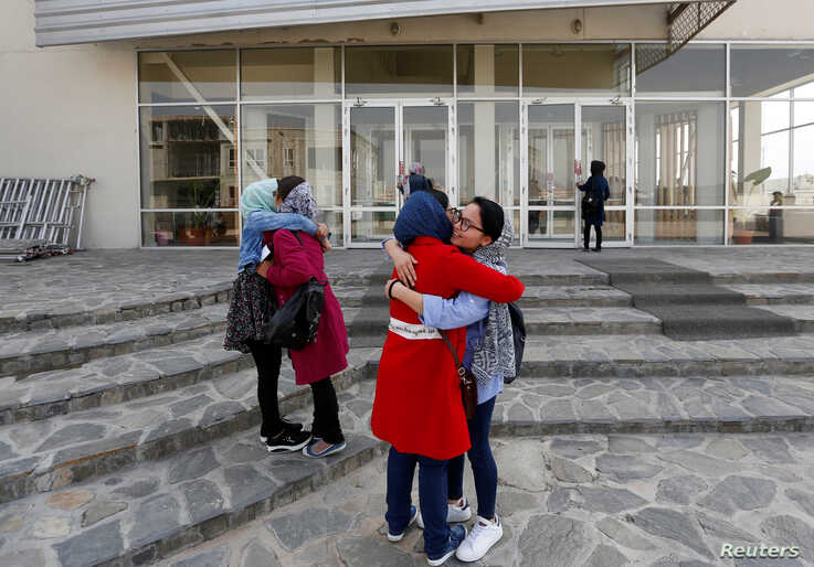 Female students of American University of Afghanistan hug each other as they arrive for new orientation sessions at a American…