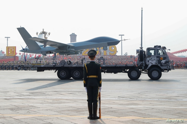 A military vehicle carrying an unmanned aerial vehicle (UVA) travels past Tiananmen Square during the military parade marking…