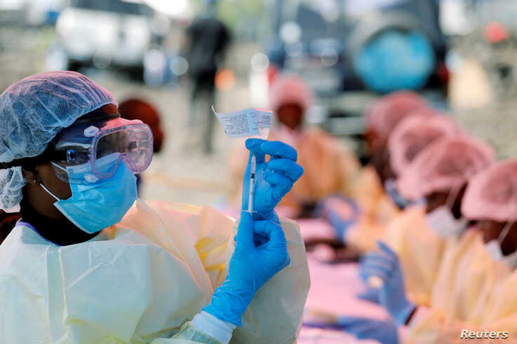 FILE PHOTO: A health worker fills a syringe with Ebola vaccine before injecting it to a patient, in Goma, Democratic Republic…