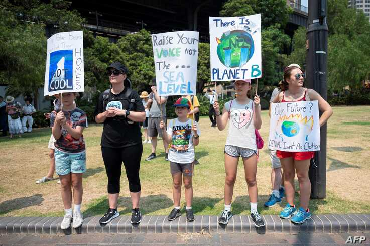 Demonstrators hold up placards during a climate protest rally in Sydney, Austalia, Dec. 21, 2019.