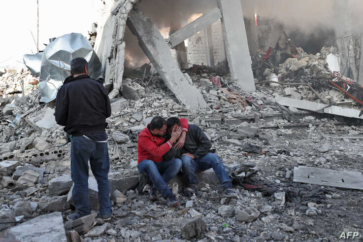 A Syrian man comforts another on the rubble of a building after a reported Russian airstrike on a popular market in the village of Balyun in Syria's northwestern Idlib province, Dec, 7, 2019.