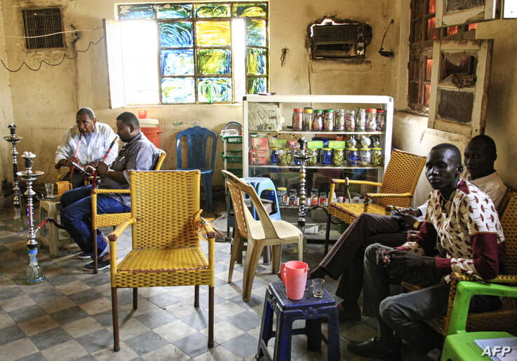 FILE - Sudanese men smoke waterpipes, also known as hookahs, at a cafe in the Sudanese capital Khartoum, Aug. 22, 2019. The consumption of alcohol has recently been decriminalized by Sudan's transitional government.