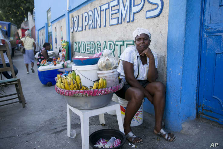 Food vendor Marie Bernard Noel sits outside the closed Center Classique Don Bosco school, in hopes it might reopen, in Petion-Ville, Haiti, Dec. 2, 2019.
