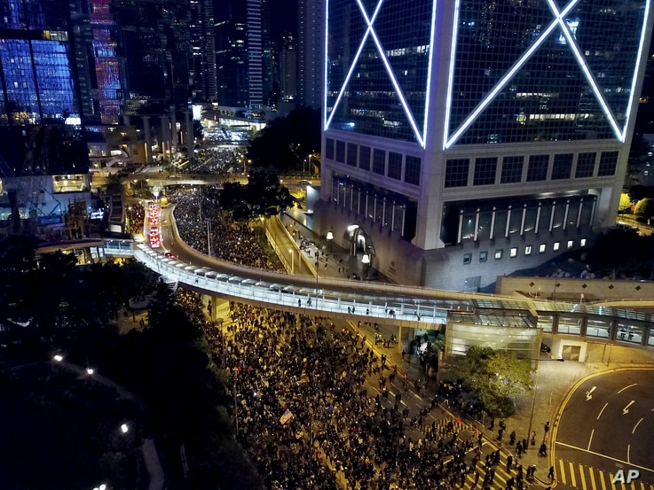 Pro-democracy protesters march into the night in Hong Kong, Dec. 8, 2019.