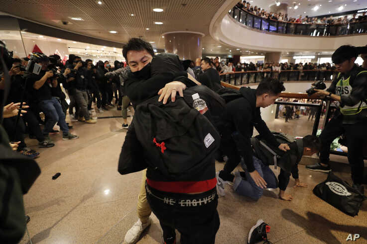 Plainclothes police officers arrest protesters in a mall during Christmas Eve in Hong Kong, Dec. 24, 2019.