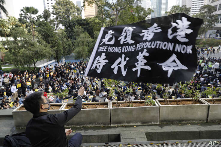 A pro-democracy supporter waves a flag during a rally by the advertising industry in Hong Kong, Dec. 2, 2019.