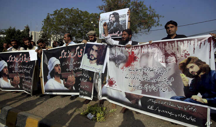 """FILE - Supporters of Naqeebullah Mehsud, who was killed by police, hold a banner that reads """"The People of Karachi Demand the Arrest of the Killers of Naqeebullah Mehsud and take the Logical End,"""" in Karachi, Pakistan, Jan. 27, 2018."""