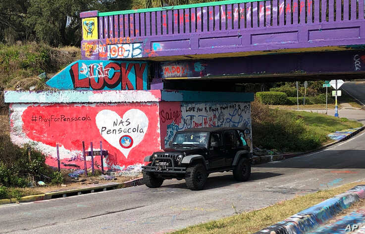A vehicle drives by a tribute to victims of the Naval Air Station Pensacola shooting, on what's known as Graffiti Bridge in downtown Pensacola, Florida, Dec. 7, 2019.