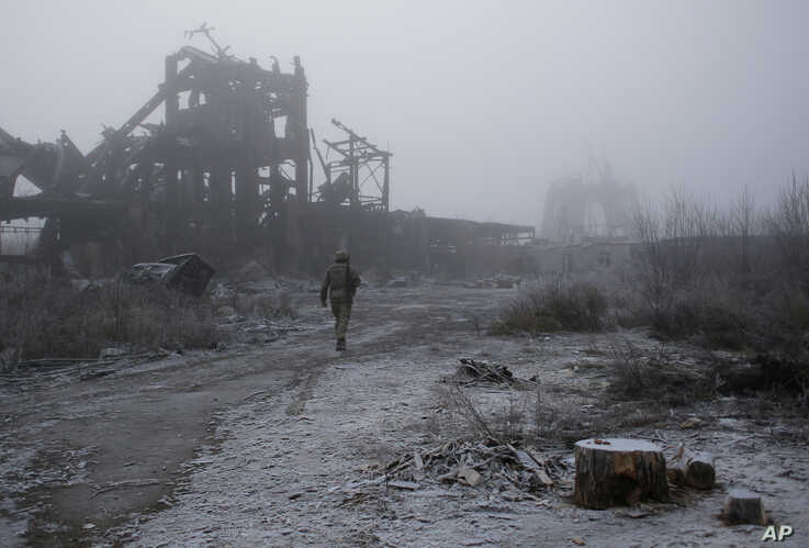 FILE - A Ukrainian soldier passes by a destroyed Butovka coal mine as he approaches a frontline position in the town of Avdiivka in the Donetsk region, Nov. 9, 2019.