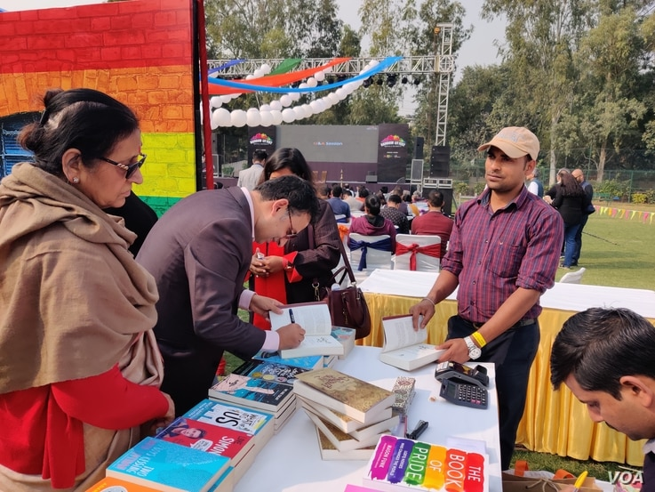 "Author and lawyer Saif Mahmood signs his book ""Beloved Delhi"" at the queer literature festival. (Anjana Pasricha/VOA)"