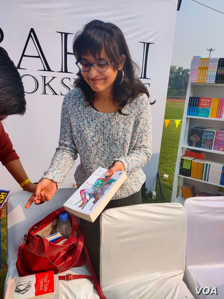Undergraduate student Divya Gulati buys a book on lesbian stories in India at the festival. (Anjana Pasricha/VOA)