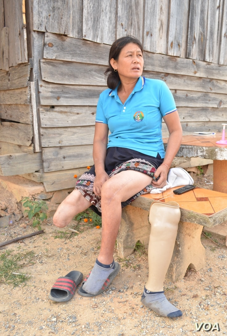 Bou Kham sits in the front yard of her home near Phonsavan, Xiangkhouang Province, Nov. 1, 2019. A U.S. cluster bomb severed her right leg five years ago when it exploded by her feet while she was collecting it from a rice field to salvage the metal. (Zsombor Peter/VOA)
