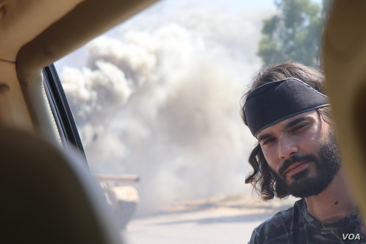 Mohammad Bashir, a GNA fighter is seen near a burning tank in Tripoli, Libya, July 7, 2019. (Heather Murdock/VOA)