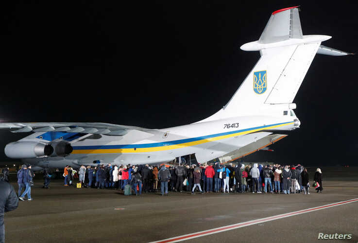 Relatives of Ukrainian citizens, who were exchanged during a prisoner swap, surround an aircraft during a welcoming ceremony at Boryspil International Airport, outside Kyiv, Ukraine, Dec. 29, 2019.