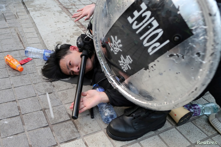 Police arrest a protester after a Chinese flag was removed from a flag pole at a rally in support of Xinjiang Uighurs' human rights in Hong Kong, China.