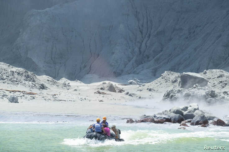 Tour guides evacuate tourists on a boat shortly after the volcano eruption on White Island, New Zealand, Dec. 9, 2019 in this picture obtained from social media.