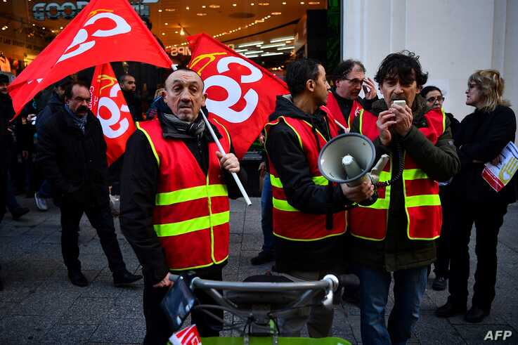 Members of the French national trade union General Confederation of Labour (CGT) distribute leaflets during a rally by the…
