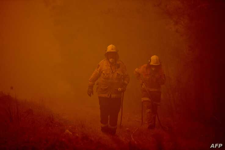 Firefighters tackle a bushfire in thick smoke in the town of Moruya, south of Batemans Bay, in New South Wales, Jan. 4, 2020.