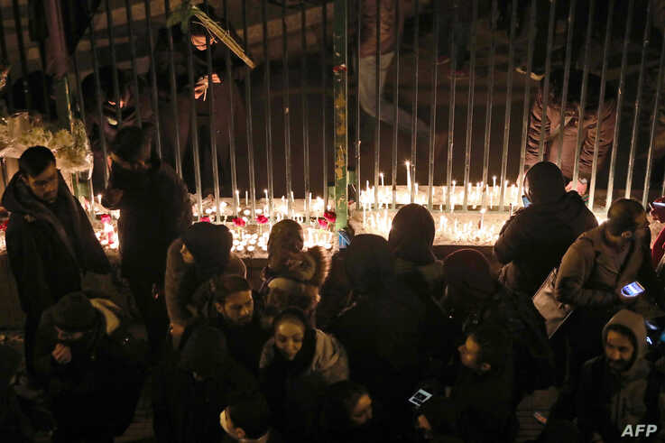 Iranians light candles for the victims of a Ukraine International Airlines crash during a gathering in front of Amirkabir University in Tehran, Jan. 11, 2020.