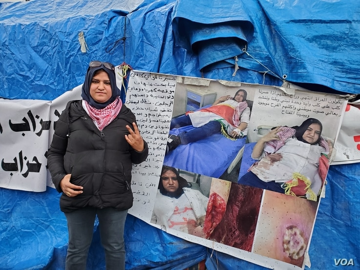 Intesar, 29, poses by photos of herself being treated after she was stabbed during a protest, pictured on  Jan. 21, 2020. (Heather Murdock/VOA)