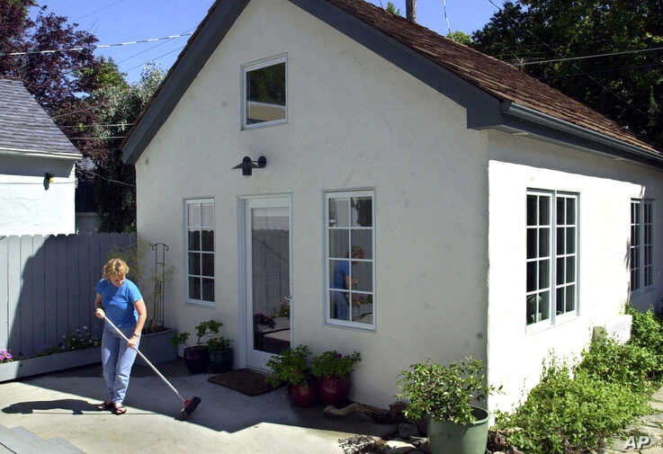 "FILE — Christine Minnehan sweeps up in front of her ""granny flat"" located in the backyard of her Sacramento, California."