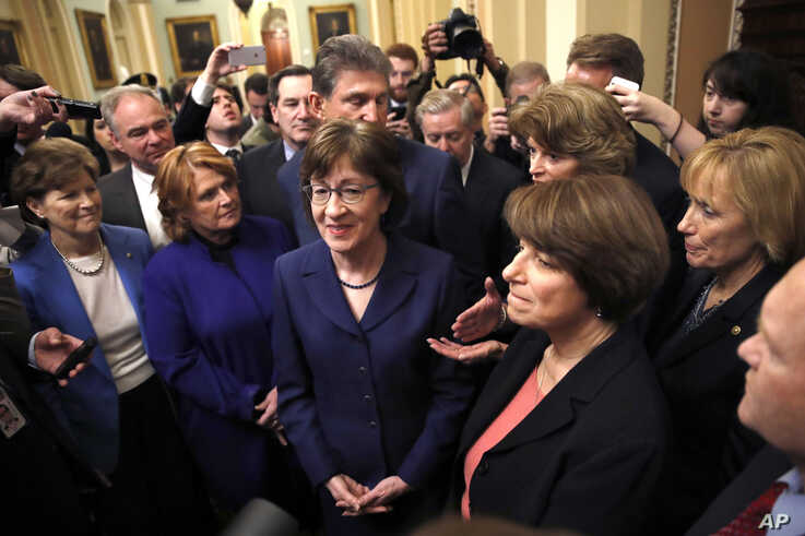 Sen. Heidi Heitkamp (2nd from left) with Sen. Susan Collins (center), Sen. Amy Klobuchar (2nd from right) at the Capitol in Washington, Jan. 22, 2018.