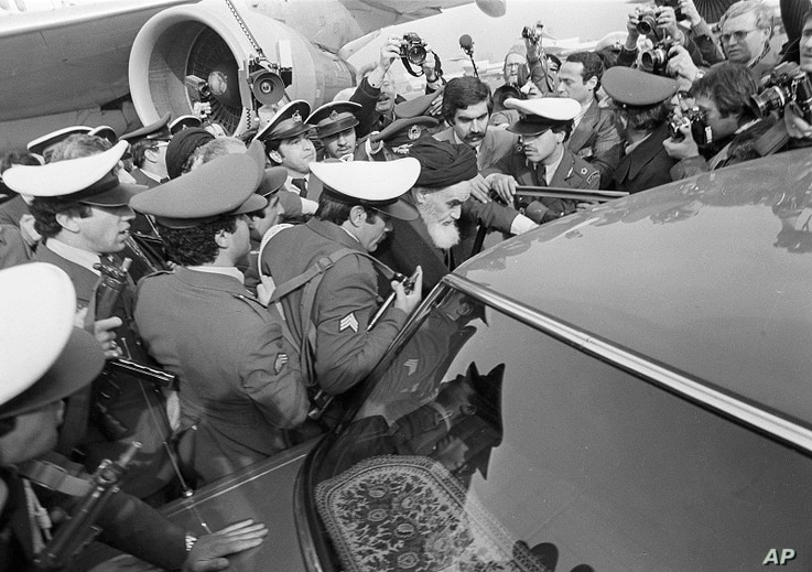 FILE - In this Feb. 1, 1979 file photo, exiled Ayatollah Ruhollah Khomeini has a heavy escort as he enters car to leave the…