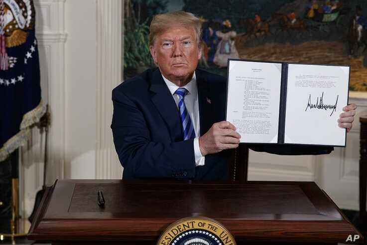 FILE - In this May 8, 2018 file photo President Donald Trump shows a signed Presidential Memorandum after delivering a...