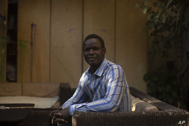 Patrice Gaudensio, a refugee artist from South Sudan poses for a portrait during an exhibition featuring work by refugee artists, at Art Cafe in Cairo, Nov. 27, 2019. He said he and his wife experienced racism and discrimination several times in Cairo.