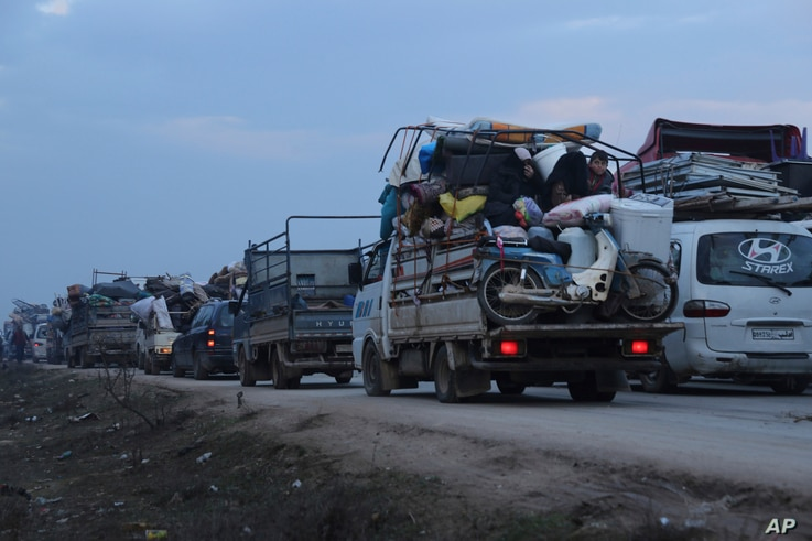 Truckloads of civilians flee a Syrian military offensive in Idlib province on the main road near Hazano, Syria, Tuesday, Dec…