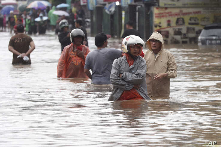 Indonesian people wade through floodwaters at Jatibening on the outskirt of Jakarta, Indonesia, Wednesday, Jan. 1, 2020. Severe…