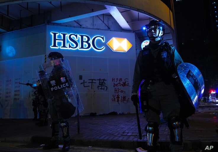Police stand guard in front of a vandalized HSBC bank on New Year's Day in Hong Kong, Wednesday, Jan. 1, 2020. Hong Kong toned…