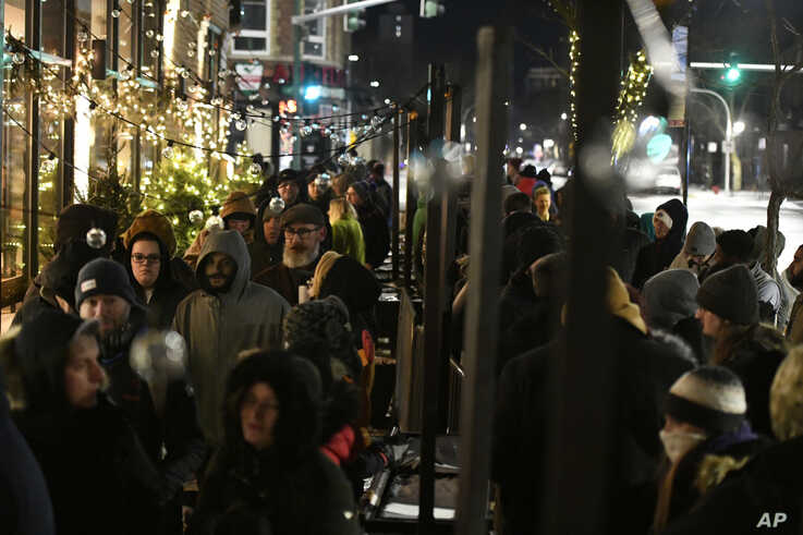 A long line of people brave the cold as they wait to be the first in Illinois to purchase recreational marijuana at Sunnyside…