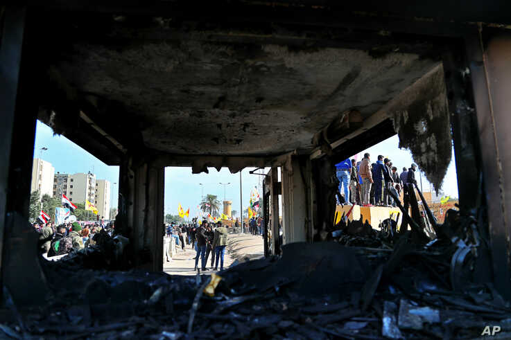 Protesters are seen through broken windows of a burned checkpoint in front of the U.S. embassy in Baghdad, Iraq, Jan. 1, 2020.