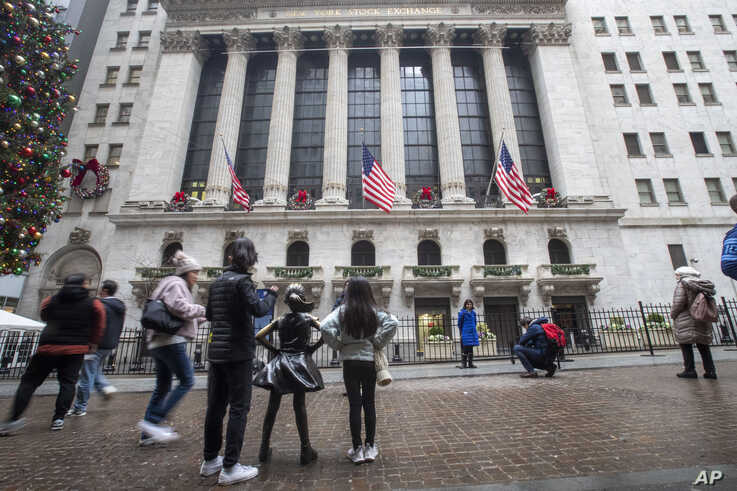 Visitors to the New York Stock Exchange pause to take photos, Jan. 3, 2020, in New York. Stocks fell broadly in midday trading and oil prices surged after U.S. forces in Iraq killed a top Iranian general.