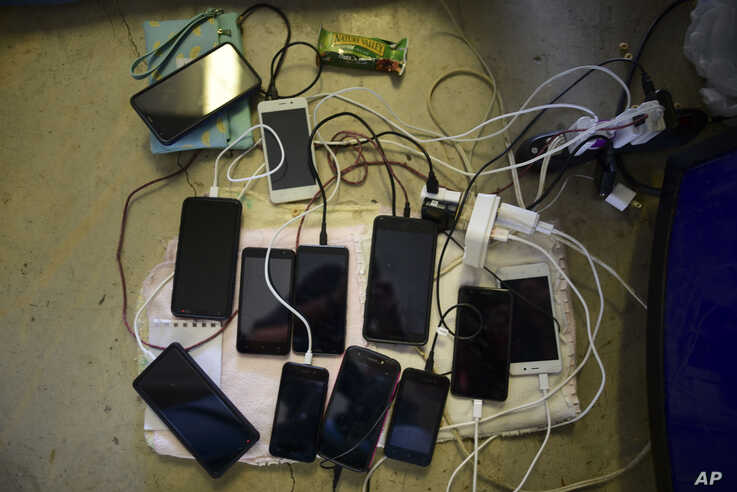Cell phones sit to charge with the use of a generator, at the Bernardino Cordero Bernard High School which is without…