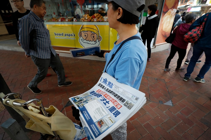"A vendor gives out copies of newspaper with a headlines of ""Wuhan break out a new type of coronavirus, Hong Kong prevent SARS…"