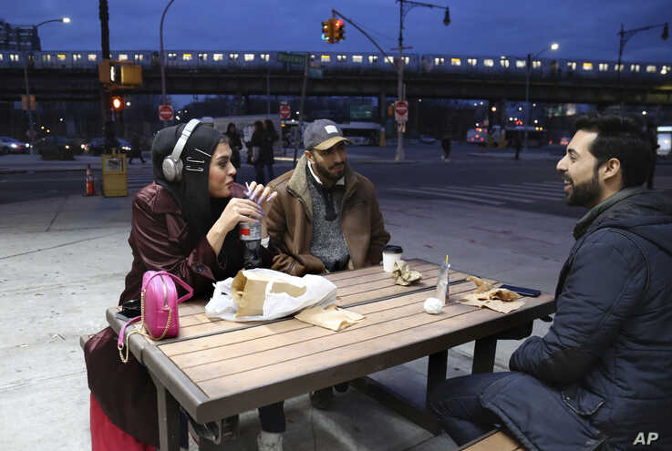 Amani Al-Khatahtbeh, founder of MuslimGirl.com, left, sips a soda while talking with old friends Mohammed Ali, right, and Saad Khan outside of a corner market in the Brooklyn borough of New York, Dec. 27, 2019.