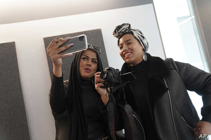 Amani Al-Khatahtbeh, left, films a video with Maryam Saad after recording a podcast pilot at Spotify's headquarters in New York, Dec. 19, 2019. Al-Khatahtbeh started the website as a way to defy Muslim stereotypes after 9/11.
