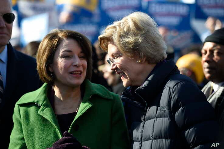 Sens. Amy Klobuchar and Elizabeth Warren speak on Jan. 20, 2020, as they line up for a Martin Luther King Jr. Day march in Columbia, S.C.