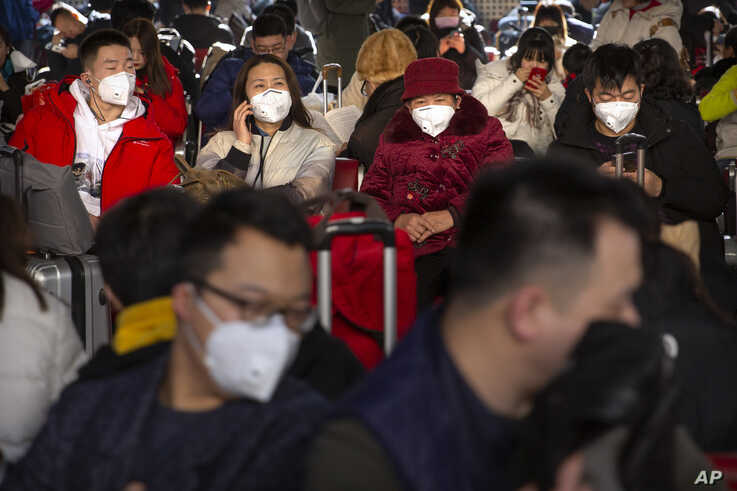 Travelers wear face masks as they sit in a waiting room at the Beijing West Railway Station in Beijing, Tuesday, Jan. 21, 2020…