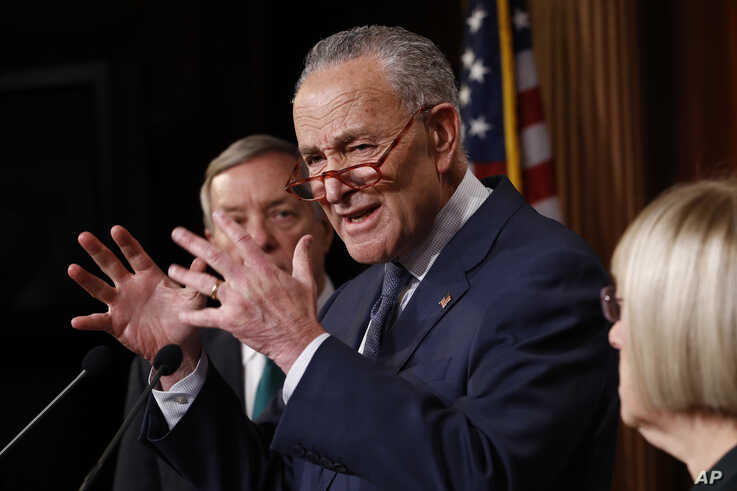 Senate minority leader, Charles Schumer, D-NY.,at podium gestures as Sen. Dick Durbin, D-Il., left, and Sen. Patty Murray.