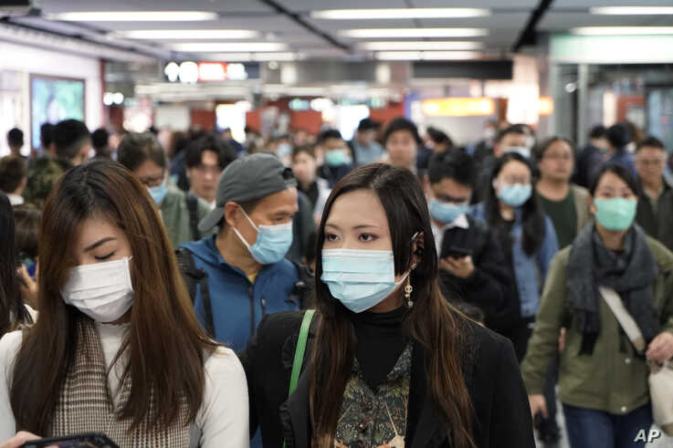 Passengers wear masks to prevent an outbreak of a new coronavirus in a subway station, in Hong Kong, Jan. 22, 2020.
