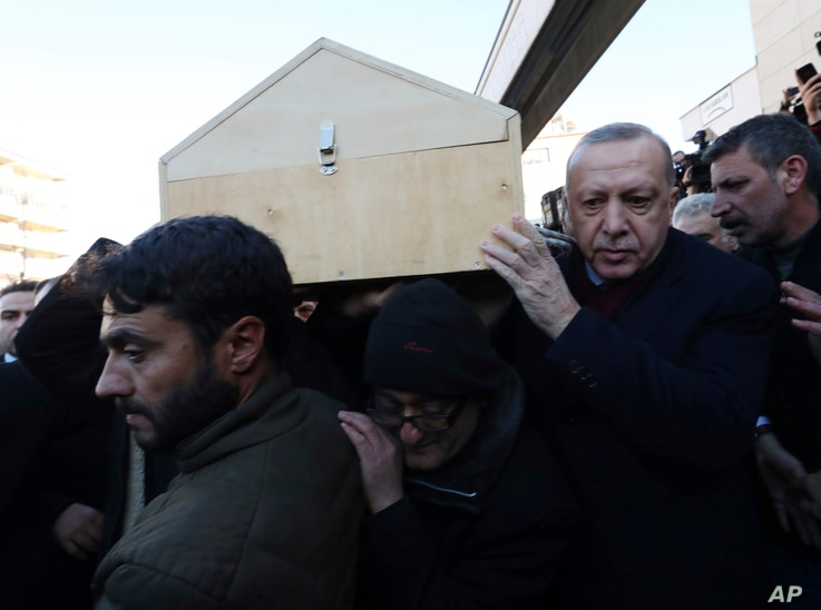 Turkey's President Recep Tayyip Erdogan carries the coffin of a victim after an earthquake hit Elazig, eastern Turkey, Friday, during the funeral procession for Salih Civelek and Aysegul Civelek, Jan. 25, 2020.